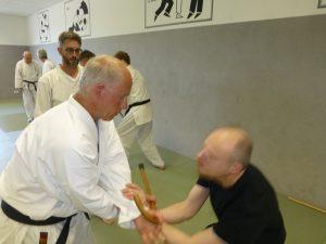 Referent Carsten Prüssner demonstriert Abwehrtechnik mit Handstock an Angelos Moshidis